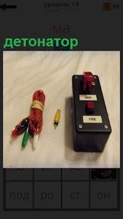 На столе лежит прибор детонатор и провода к нему для подключения