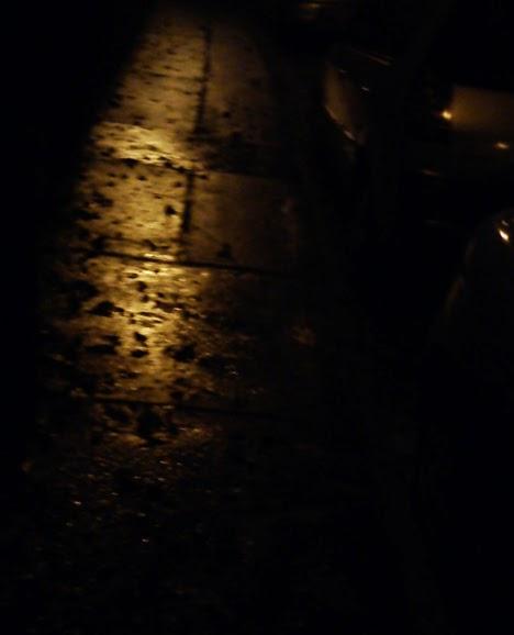 Egyértelműen komor hangulatú éjszakai utca egy esős, ködös napon, a tócsákban ázott faleveleket megvilágító lámpa fénye tükröződik homályosan.