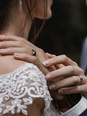 Mano del novio sobre el hombro de la novia y las de ellas sonteniéndola con cariño