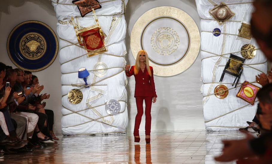 Italian fashion designer Donatella Versace acknowledges the applause of the audience at the end of the Versace men's Spring-Summer 2015 collection, part of the Milan Fashion Week, unveiled in Milan, Italy, Saturday, June 21, 2014.