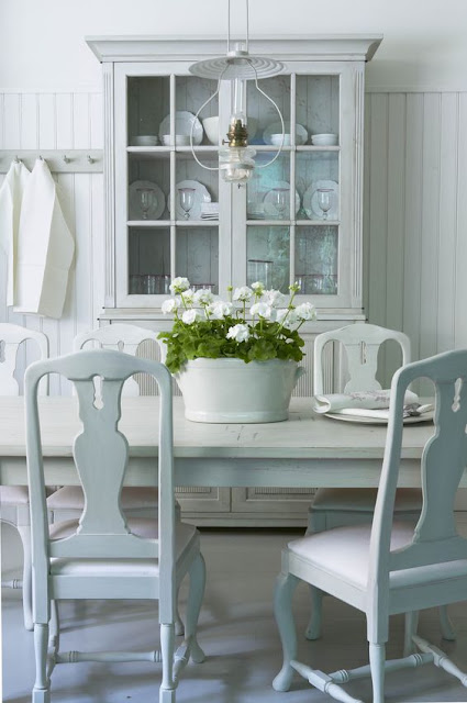 Breathtaking beautiful Swedish style dining room with glass front cabinet and calm, peaceful decor - found on Hello Lovely Studio