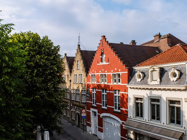 View from a window in Bruges overlooking beautiful buildings in the city centre.