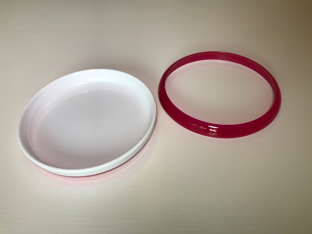 A white plastic circular plate next to a bright pink plastic ring which can attach to the top of the plate to provide a lip