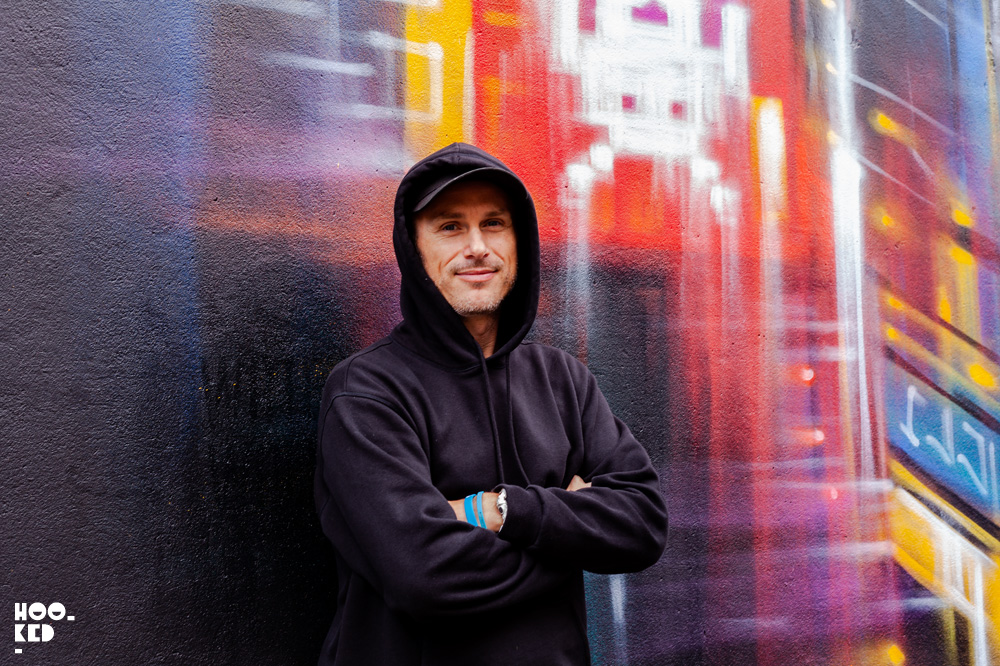 Portrait of artist Dan Kitchener in front of his finished mural at Waterford street art festival