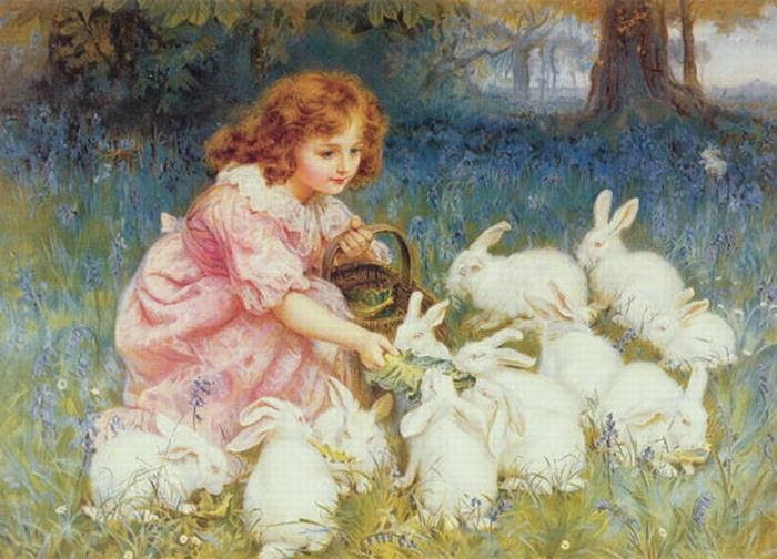 A little girl is feeding rabbits in the forest