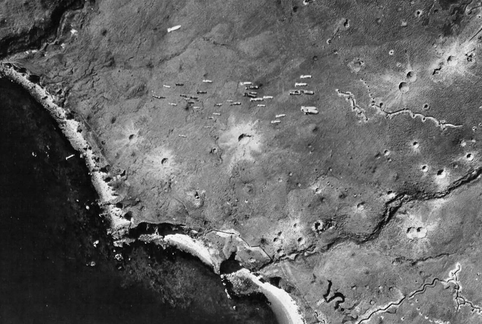 Dozens of bombs fall from a U.S. bomber toward Japanese-occupied Kiska Island, Alaska, on August 10, 1943. Note the craters from previous bombing runs and the zig-zag trenches dug by the Japanese.