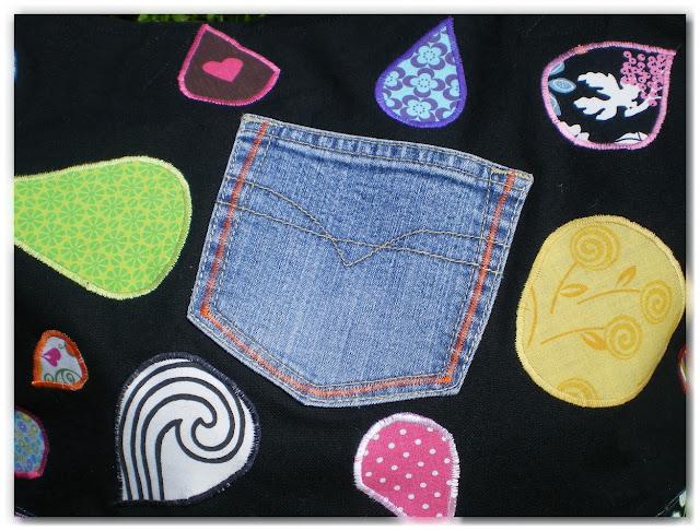 tissu noir avec appliqués en tissu colorés en forme de gouttes et poche en jean