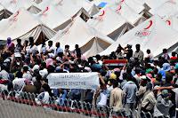 Kızılay çadırları önündeki üzerinde Türkiye'ye teşekkür eden pankart açmış Suriye'li mülteciler