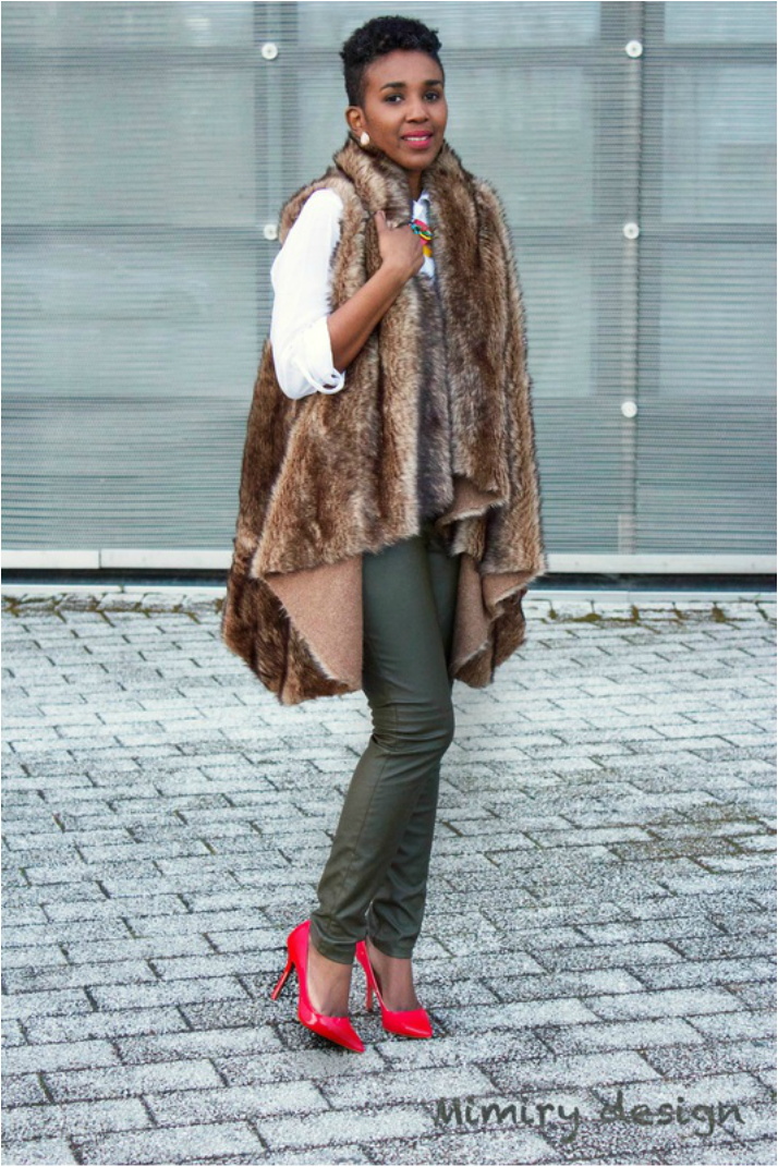 woman wearing faux fur coat, green leather pants and red pumps