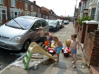 shirtless kids washing car from buckets