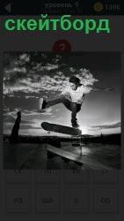 Паренек катается на доске по земле как на скейтборде, подняв одну ногу и руки в стороны