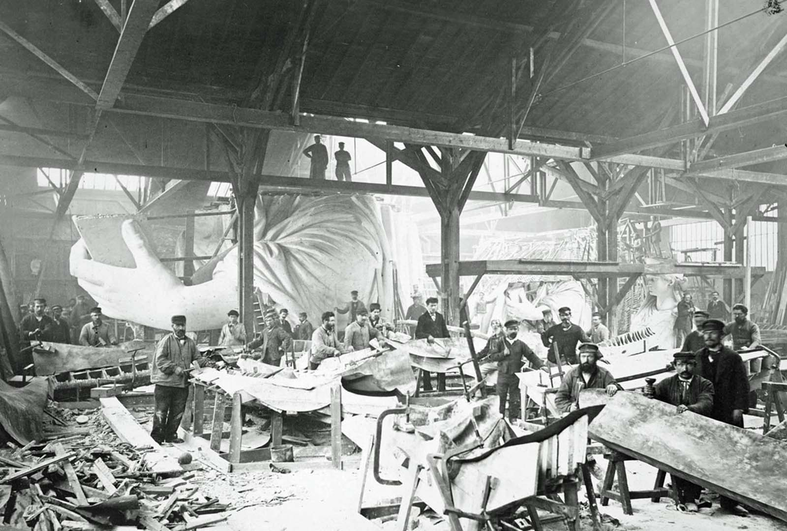 Men in a workshop hammer sheets of copper for the construction of the Statue of Liberty in 1883.