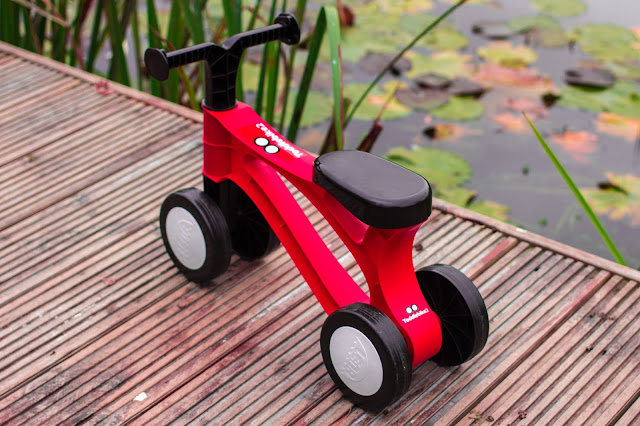 The toddlebike2 in red on decking next to a pond