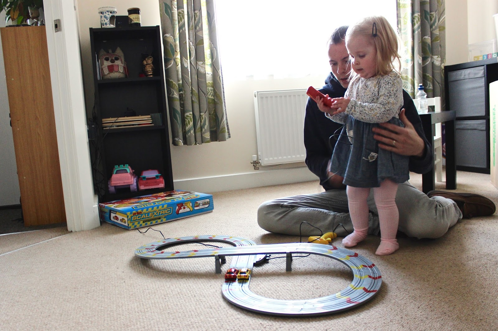 Elise is stood up next to the Scalextric track holding the red trigger. My husband is sat down behind her with his hands on her waist. The two cars are on the track in a stationary position.