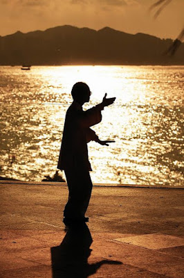 A man performing tai-chi at sunrise on the beach