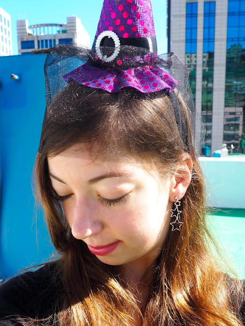 Witch Halloween Outfit | accessory details of small purple witch hat wth black veil on a headband, and silver star dangly earrings