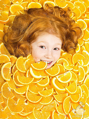Fotografía niña con naranja