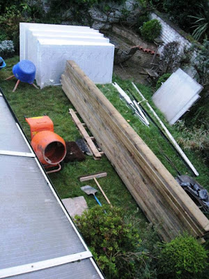 The garden strewn with panels, joints, cement mixer, insulation and rubbish