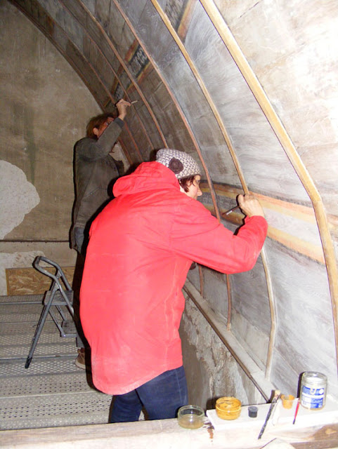 Wall paintings conservators working on the vaulted ceiling of a medieval chapel, Indre et Loire, France. Photographed by Susan Walter. Tour the Loire Valley with a classic car and a private guide.