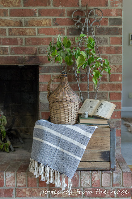 striped throw blanket and wicker demijohn on old wooden milk crate