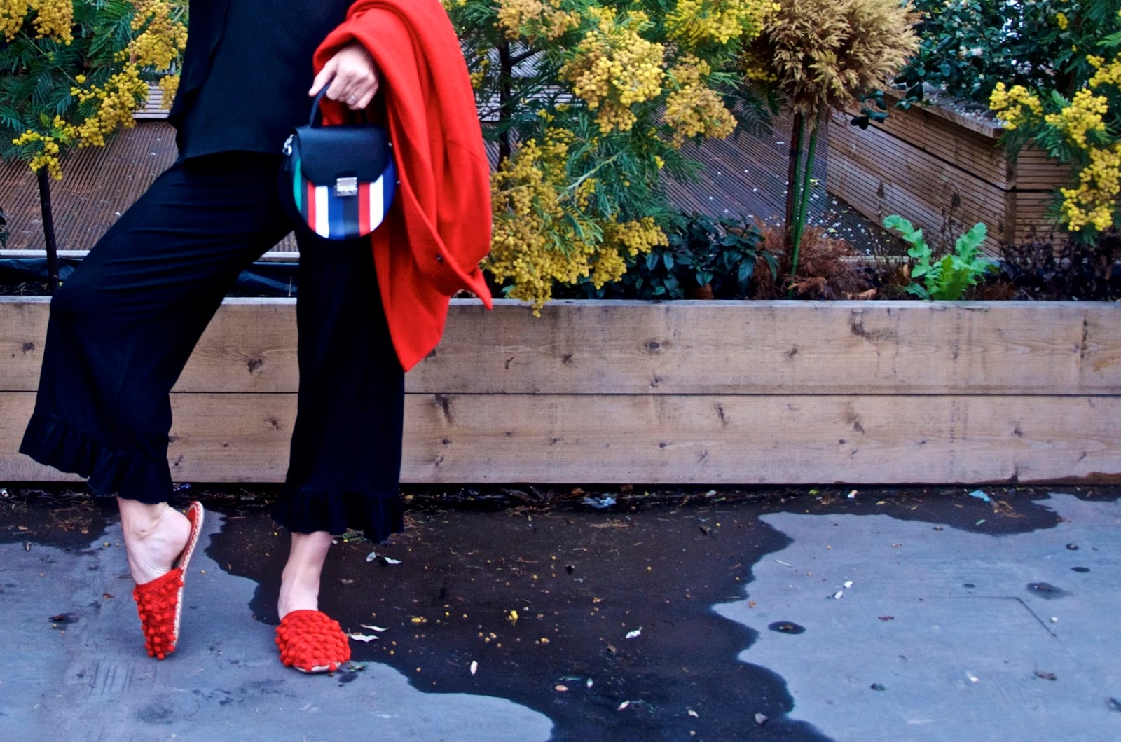 Black trousers with ruffle hem, red slip-on shoes, striped bag, red coat