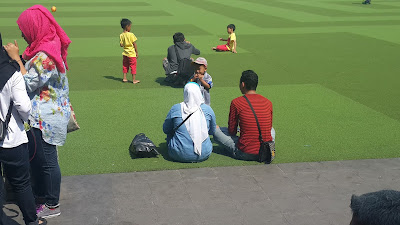 sebuah keluarga kecil sedang bersantai di alun alun bandung