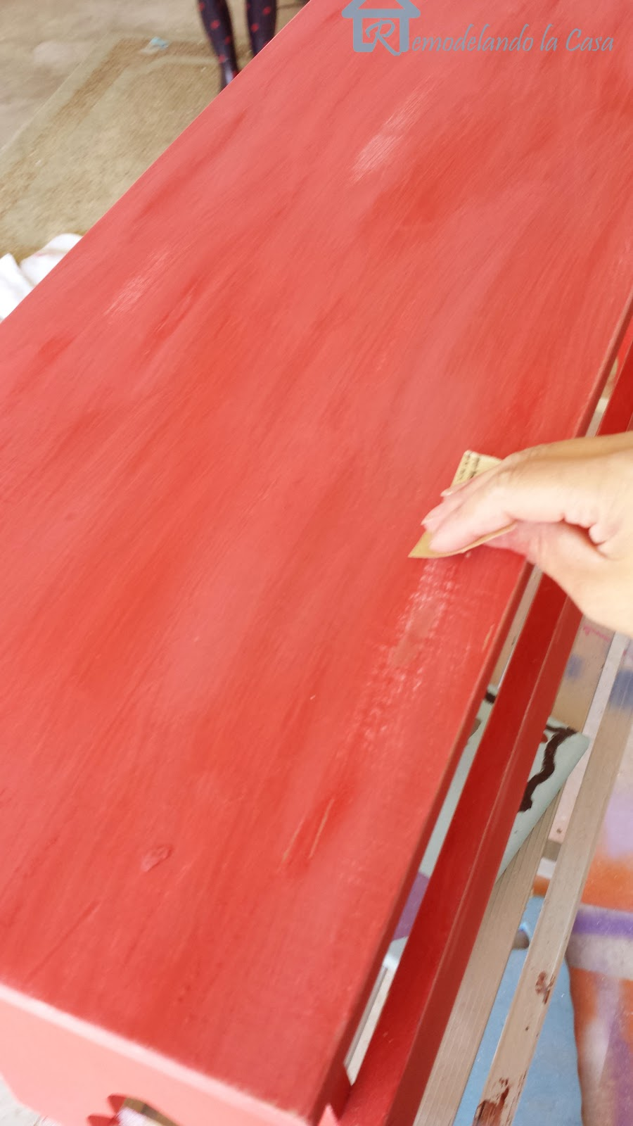 sand paper used to distress red painted bench