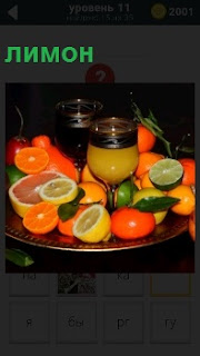На подносе лежит лимон и напиток сделанный из него. Другой стакан с напитком красного цвета
