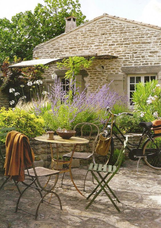 Decorating ideas & home decor: #Frenchfarmhouse courtyard with mismatched #bistrochairs and #vintagebicycle on Hello Lovely Studio