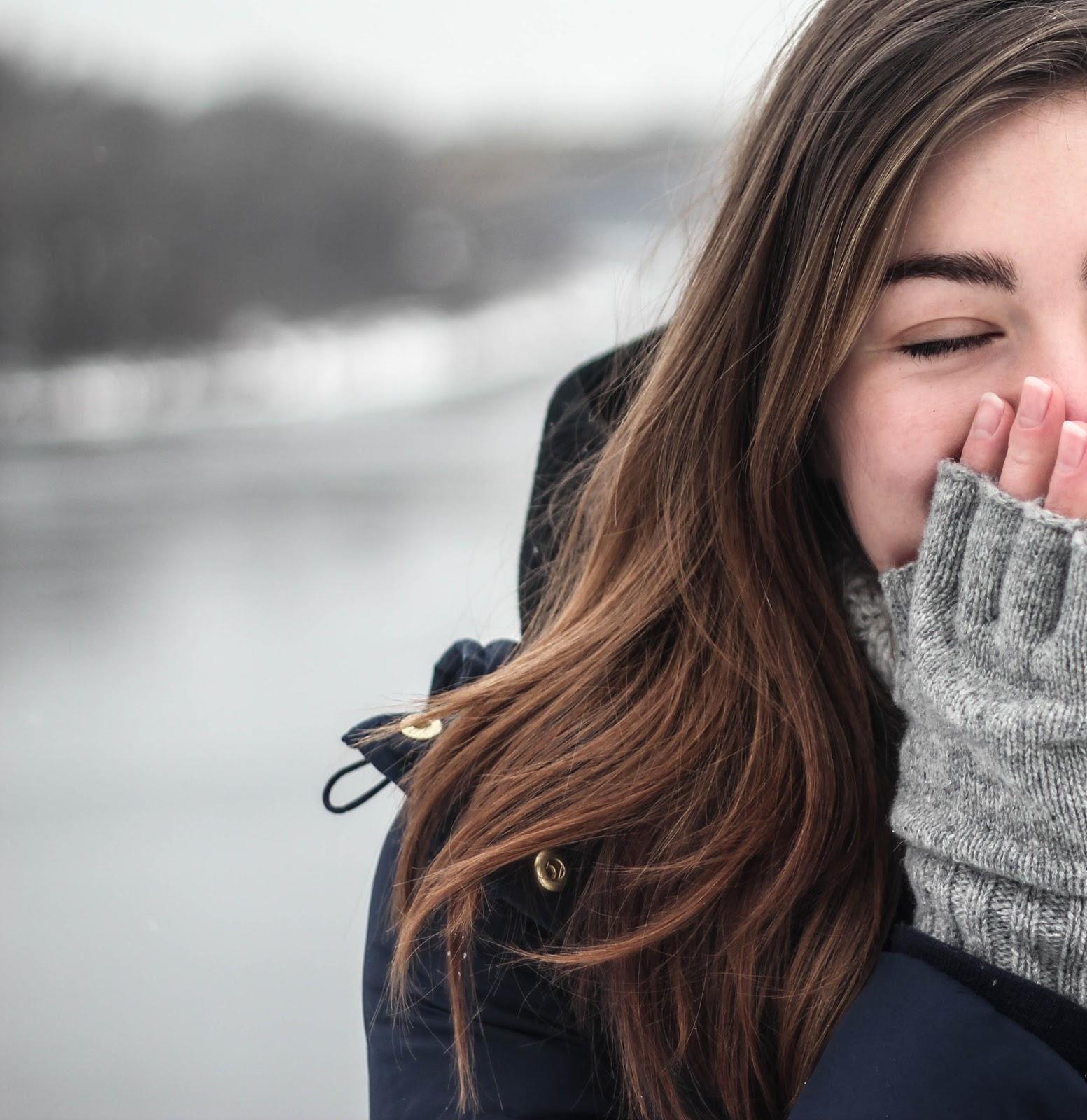 手で口を覆った笑顔の女性