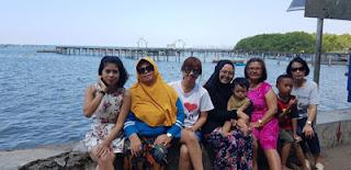 Dhanik dan keluarga di Dermaga Gundil dengan latar Kampung Kerapu Situbondo