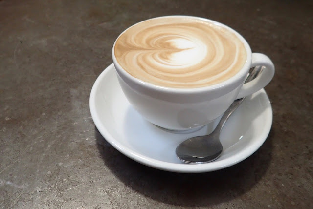 coffee in a white cup and saucer with a spoon for $4 NZD