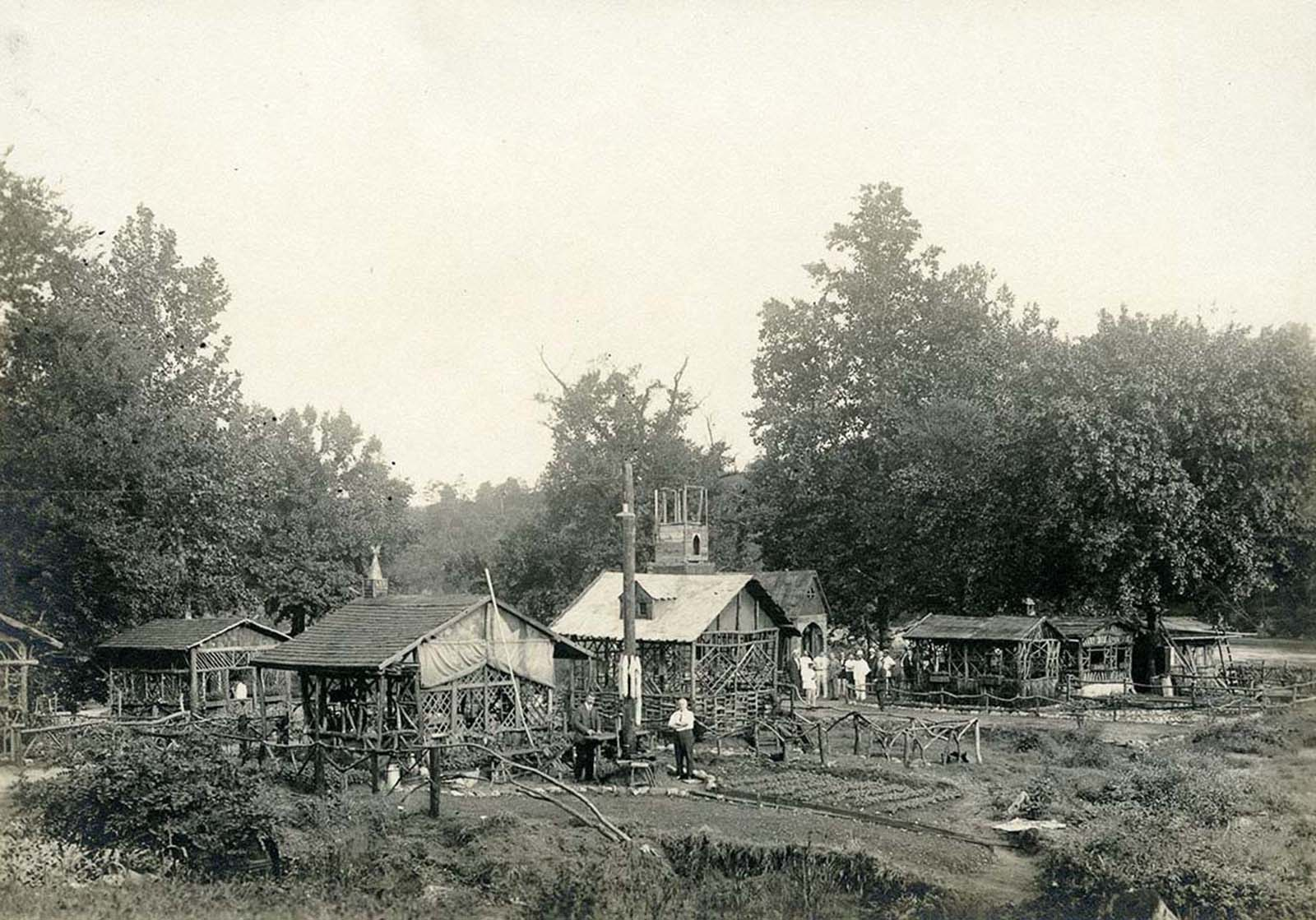 View of houses, gardens, a partially- constructed church, and German campers posing for a photograph in the German internment camp.