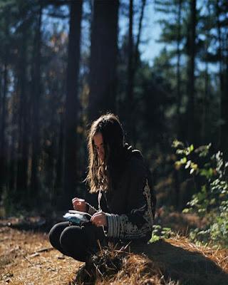 foto sentada leyendo libro en el bosque