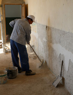 Sweeping up the dust from the walls and ceiling