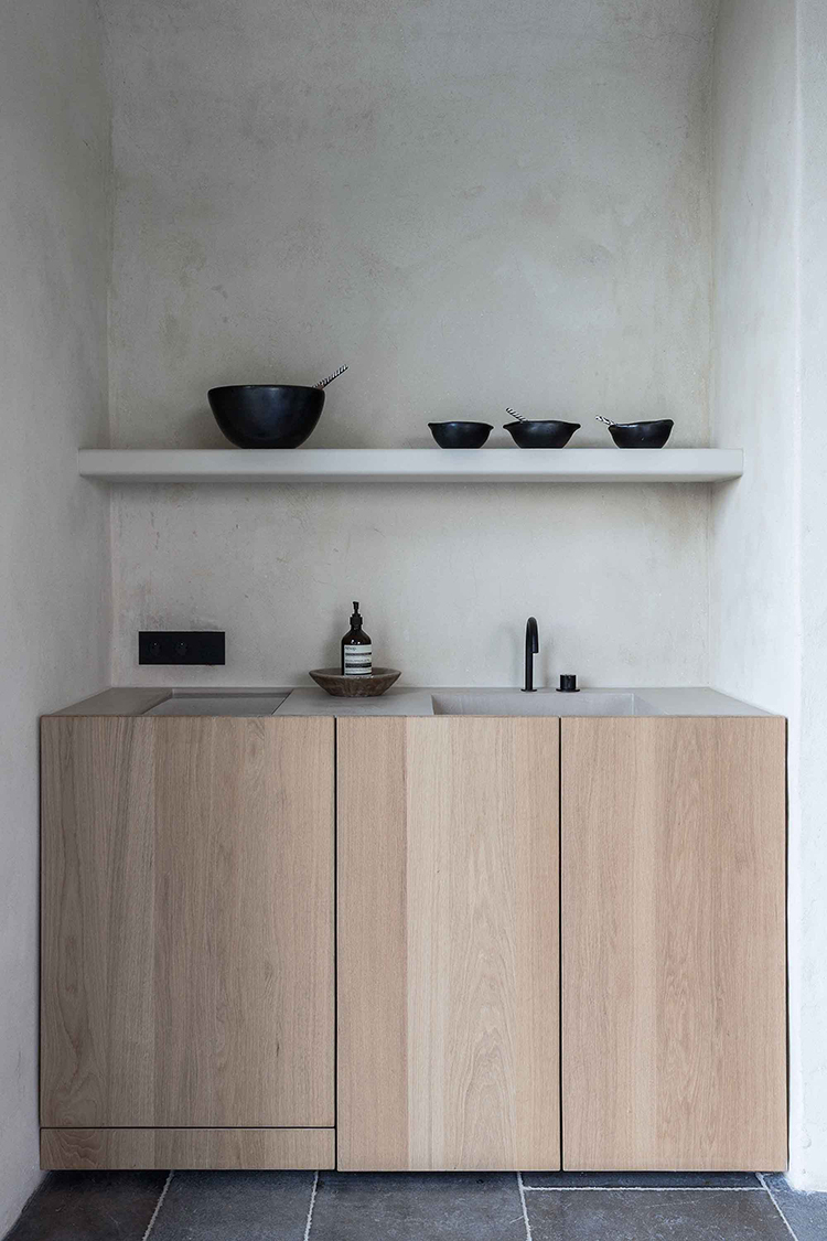 Succo walls in the kitchen, open shelves in the kitchen, black kitchen fixtures, concrete countertop, black kitchen accents, minimalist wooden cabinetry, stone floor tiles by Painted Creations bvba