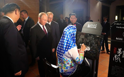 Vladimir Putin at the exhibition of Chinese arts and crafts.