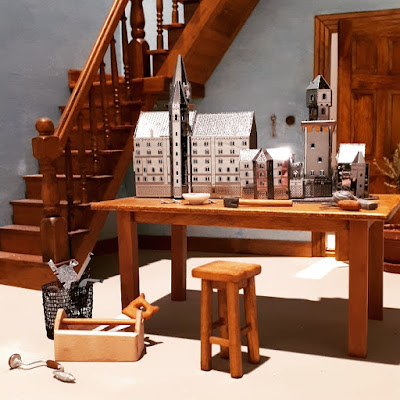 One-twelfth scale miniature room with a worktable in the foreground containing miniature metal model buildings, and a selection of tools.