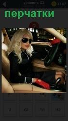 В салоне автомобиля сидит блондинка в красных перчатках и в очках, одной рукой на руле