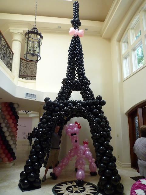 Eiffel tower sculpture from balloons and pink poodle balloon character