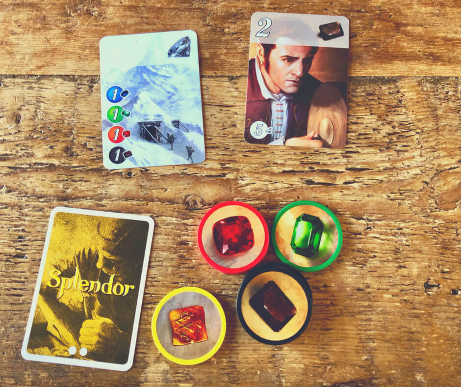 Splendor board game cards and tokens set on a wooden table.