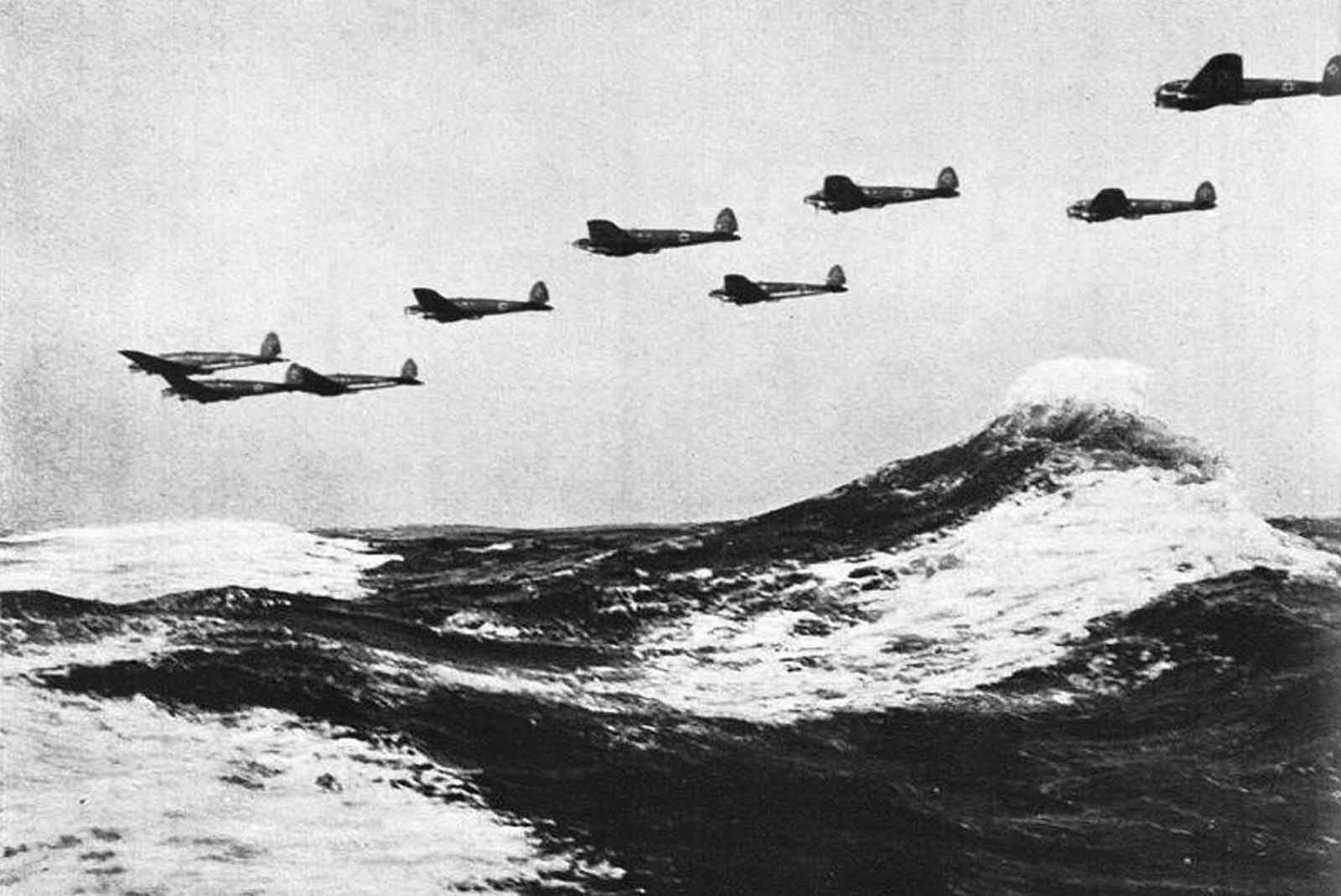 A formation of low-flying German Heinkel He 111 bombers flies over the waves of the English Channel in 1940.