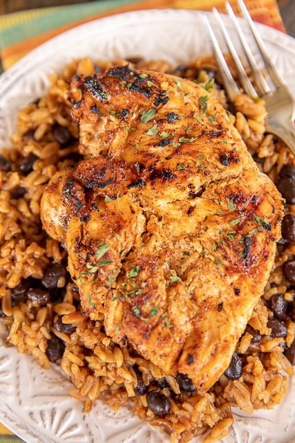grilled chicken on top of rice and beans on a plate