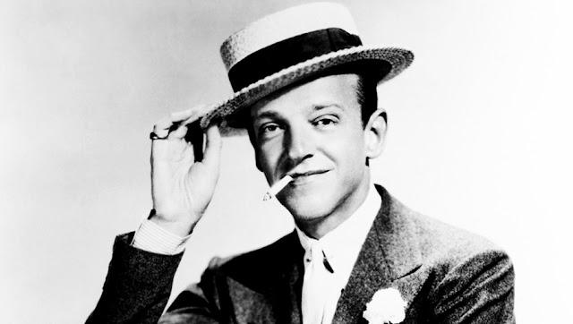 Fred Astaire vestido de traje, con sombrero y fumando
