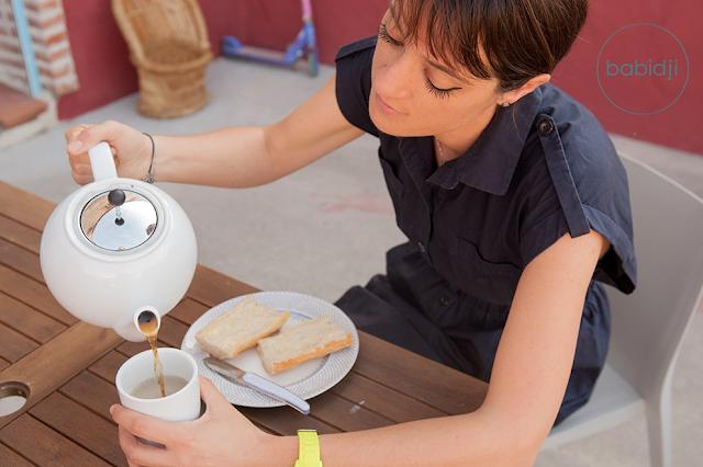 femme qui prend son petit dej sur sa terrasse en se servant un thé