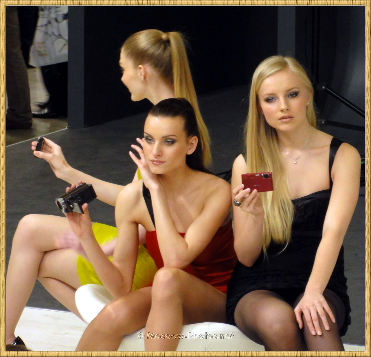 Fashion Models Posing With Digital Cameras