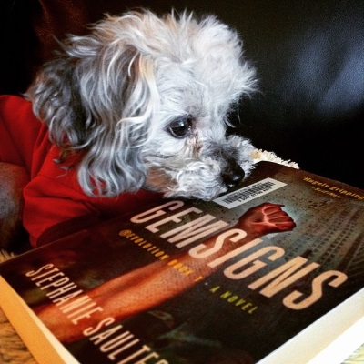 Murchie rests his chin on a trade paperback copy of Gensigns. The cover features a glowing, pale skinned fist raised in the air. Behind it, mostly obscured by debris-filled air, a hoard of people stand below tall office towers.