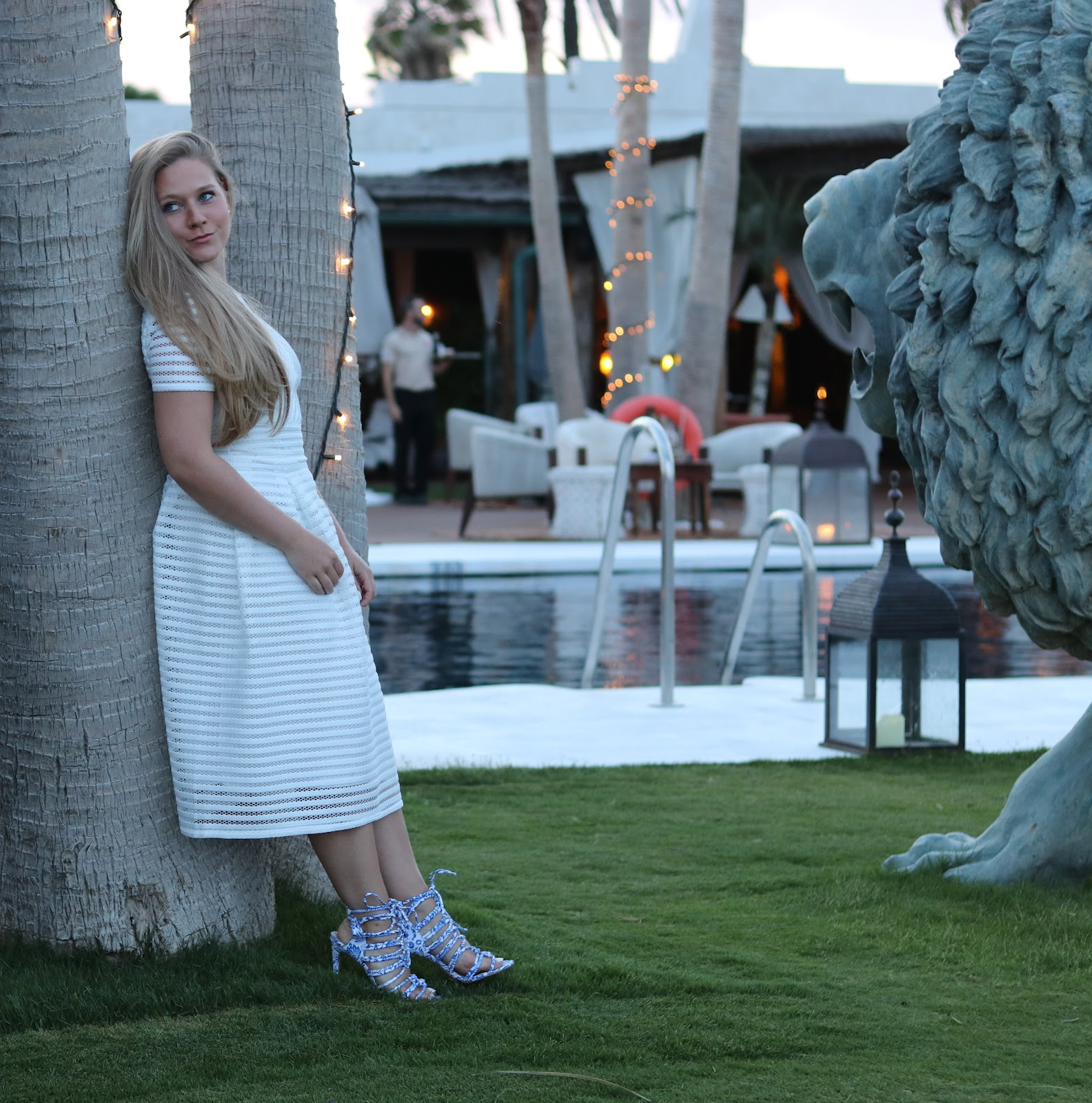 Katie Heath wearing a Boohoo dress leaning against a palm tree at Trocadero in Sotogrande, Spain