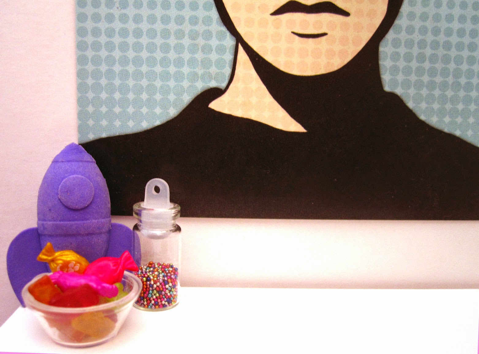 Modern dolls house miniature scene of a purple rocket, bowl of colourful sweets and jar of tiny beads in front of a colourful poster.