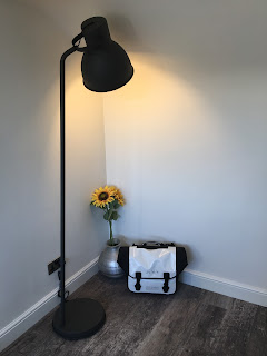 Brompton O Bag in the corner of a room with lamp and sunflowers